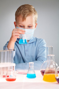 A Little Boy In Mask Looking At Liquid In Flask