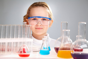 Close-up Portrait Of A Smart-looking Girl Behind The Table With Flasks And Test-tubes