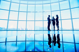 Outlines Of Successful Business Partners Standing Against Window In Office Building And Interacting