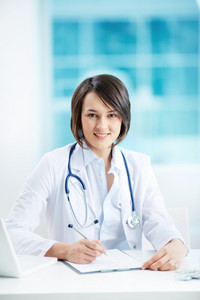 Vertical Portrait Of A Young Female Doctor At Her Workplace
