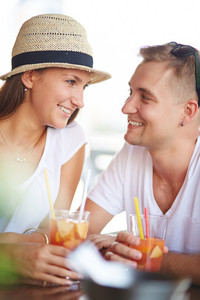 Happy Guy And His Girlfriend Chatting While Spending Time In Cafe