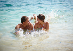 Cheerful Couple Splashing In Water At Resort