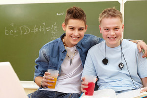 Portrait Of Smart Teenage Guys With Plastic Glasses Of Juice Looking At Camera