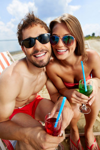 Relaxed Young Couple With Refreshing Drinks Sitting On Beach