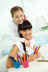 Portrait Of Lovely Girl And Her Mother With Colorful Pencils Looking At Camera
