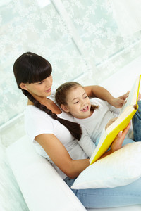 Portrait Of Cute Girl And Her Mother Reading A Book At Home