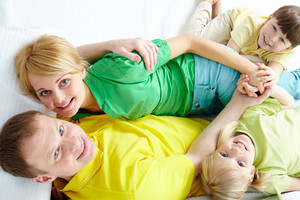 Above Angle Of Young Family Looking At Camera And Smiling