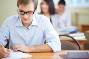 Portrait Of Group Of Students Making Notes Or Writing Test With Serious Guy In Front
