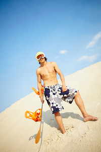 Vertical Image Of A Muscular Young Man Sandboarding