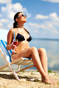 Relaxed Young Female With Drink Enjoying Rest On The Beach On A Sunny Day