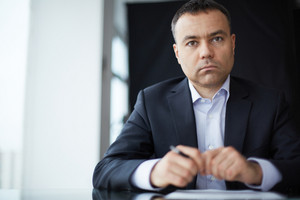 Serious Businessman Looking At Camera At Workplace
