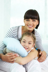 Portrait Of Happy Girl And Her Mother Looking At Camera With Smiles