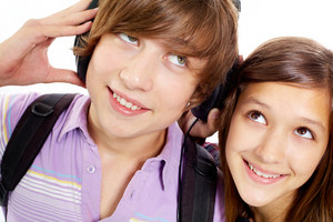 Portrait Of Happy Teenagers With Headphones Listening To Music