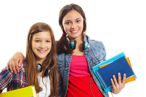 Cute Teenage Girls With Headphones And Books Smiling At Camera