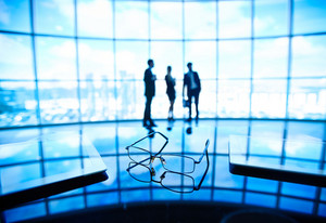 Image Of Eyeglasses And Touchpads At Workplace With Businesspeople Standing On The Background