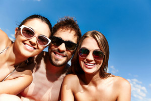 Group Of Young Friends In Sunglasses Looking At Camera Against Blue Sky