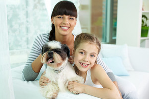 Portrait Of Happy Girl Holding Pet And Looking At Camera With Her Mother Near By