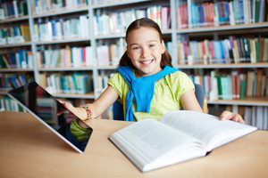 Portrait Of A Lovely Girl With Touchpad And Open Book Sitting In Library