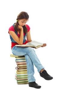 Cute Girl Reading While Sitting On Heap Of Books