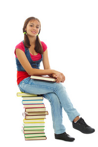 Cute Girl Sitting On Heap Of Books And Looking At Camera