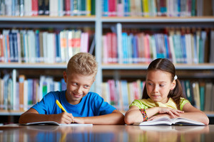 Portrait Of Diligent Schoolchildren Sitting At Lesson