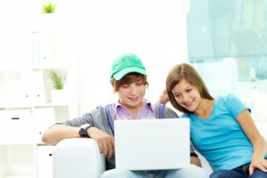 Teen Friends Hanging Out Together At Home With A Laptop