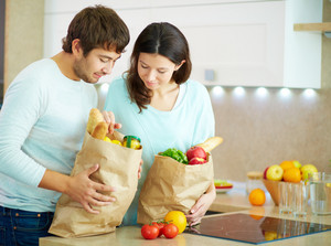 Pretty Female And Her Husband Looking At Products In Paperbags In The Kitchen