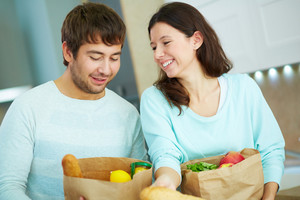 Pretty Female And Her Husband With Paper Packets In The Kitchen