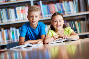 Portrait Of Cute Schoolchildren Looking At Camera While Sitting In Library