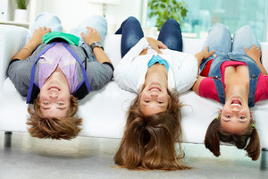 Portrait Of Three Happy Friends Having Fun On Sofa