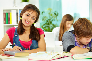 Portrait Of Smart Girl Looking At Camera During Lesson With Classmates Near By