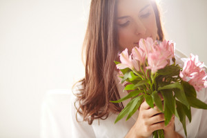 Portrait Of Lovely Lady Looking At Bunch Of Flowers In Her Hands