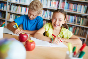 Portrait Of Cheerful Schoolgirl Looking At Camera While Sitting In Library With Her Classmate Near By