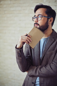 Pensive Businessman With Notepad Brainstorming