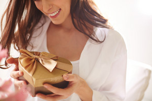 Close-up Of Smiling Female Holding Heart Shaped Giftbox