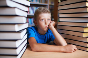 Portrait Of Bored Schoolkid Looking At Camera Surrounded By Stacks Of Books
