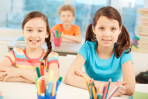 Portrait Of Two Diligent Girls Looking At Camera At Workplace With Schoolboy On Background