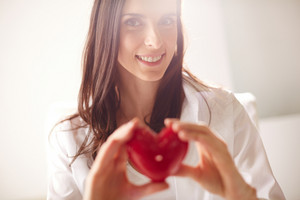 Image Of Smiling Female With Red Heart In Hands Looking At Camera