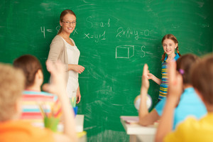 Portrait Of Smart Teacher And Schoolgirl Standing By Blackboard And Looking At Schoolkids In Classroom