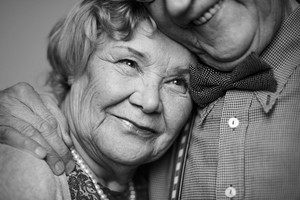 Black-and-white Image Of Senior Female Being Embraced By Her Husband