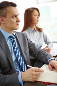 Serious Businessman In Suit And His Female Partner Sitting At Conference