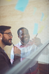 African Businessman Pointing At Reminder While Explaining Idea To Colleague In Office