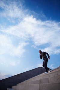 Portrait Of Young Sportsman Running Down Steps Against Cloudy Sky