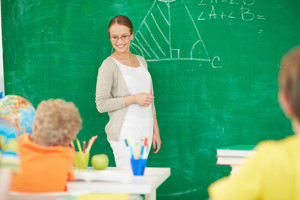 Portrait Of Smart Teacher Standing By Blackboard And Looking At Schoolkids