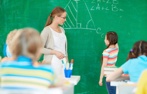 Portrait Of Smart Teacher Standing By Blackboard And Looking At Cute Girl Explaining Solution