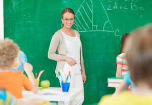 Portrait Of Smart Teacher Standing By Blackboard And Looking At Schoolkids While One Of Pupils Standing Near By