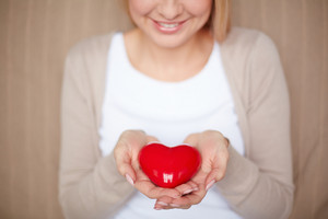 Close-up Of Smiling Female Holding Red Heart On Palms