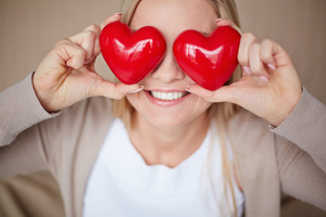 Image Of Smiling Female With Two Red Hearts By Her Eyes