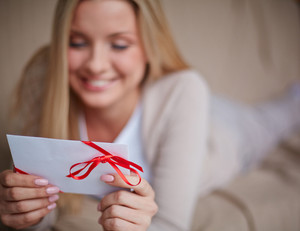 Image Of Smiling Female Holding Valentine Letter And Looking At It