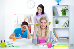 Portrait Of Clever Teenage Blonde Raising Arm At Lesson In Working Environment